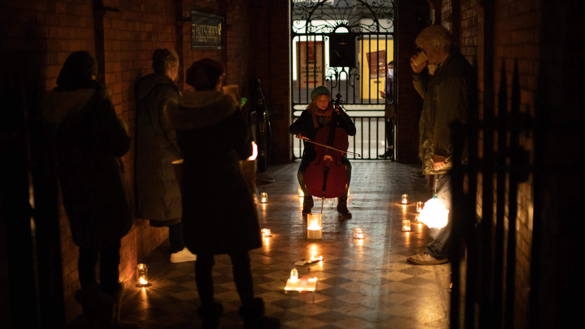 In a dark alley with red brick walls and a black and white tiled floor. A young woman sits wrapped up in wither clothes playing a cello. She is surrounded by candles in glass jars. A small socially distanced audience watch her sipping warm drinks