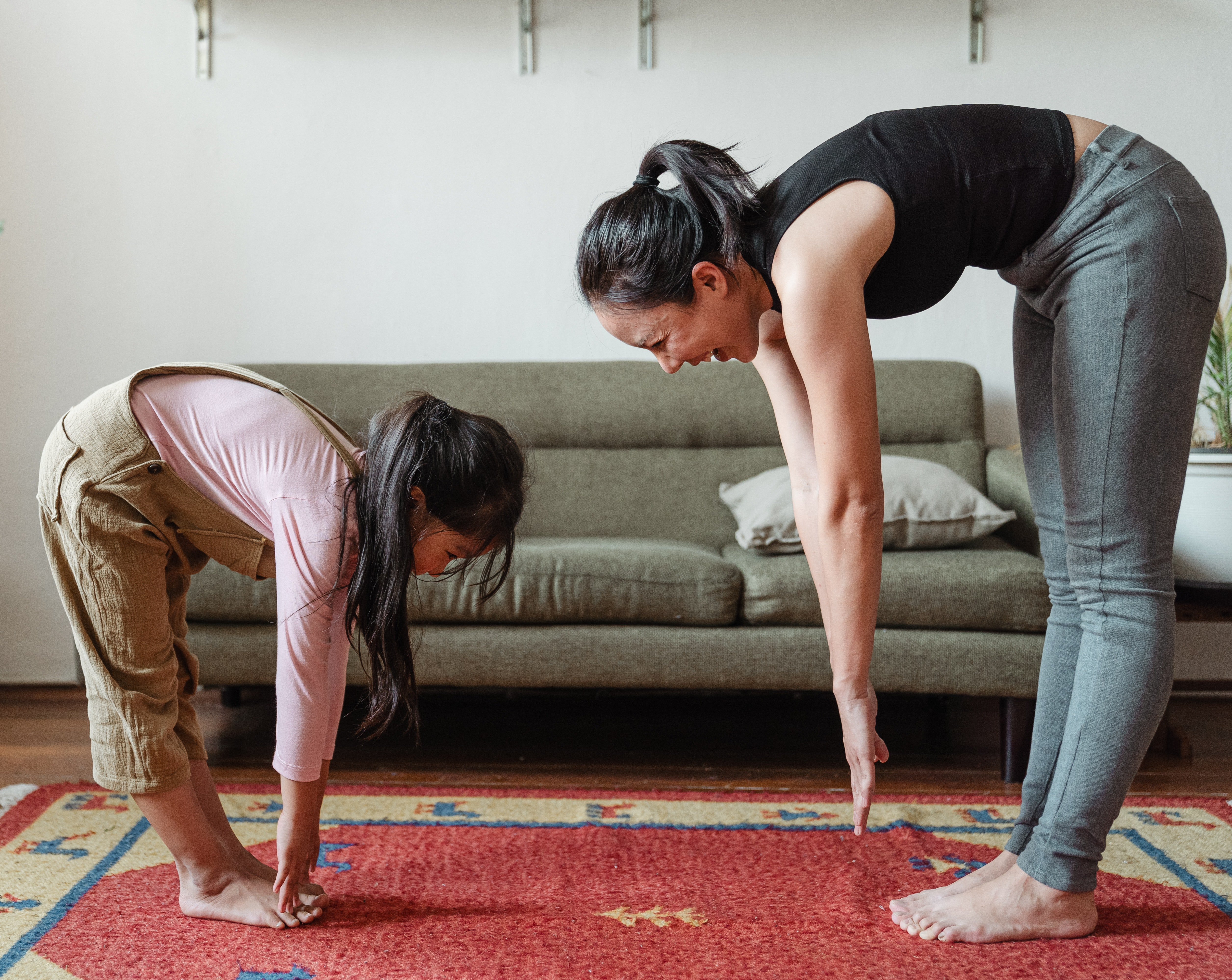 Woman and daughter stretching together.