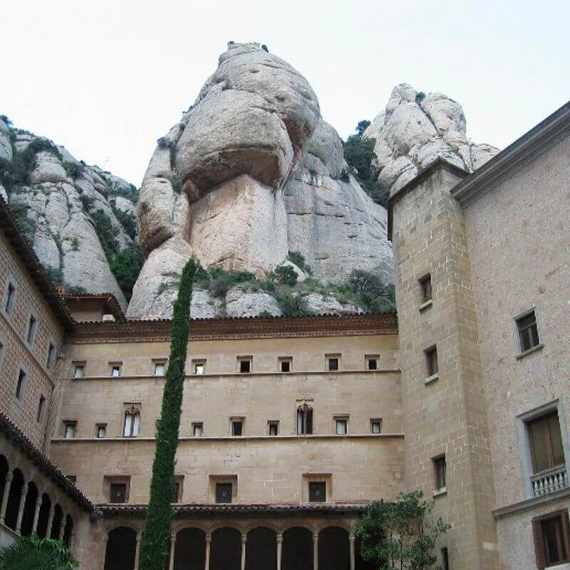 Montserrat Monastery - a very tall house, behind which are large, high rocks.