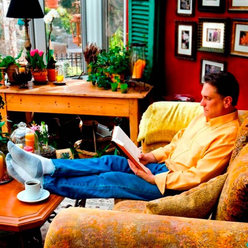 A man sits on a couch indoors with lots of potted plants, pictures, and warm colors.