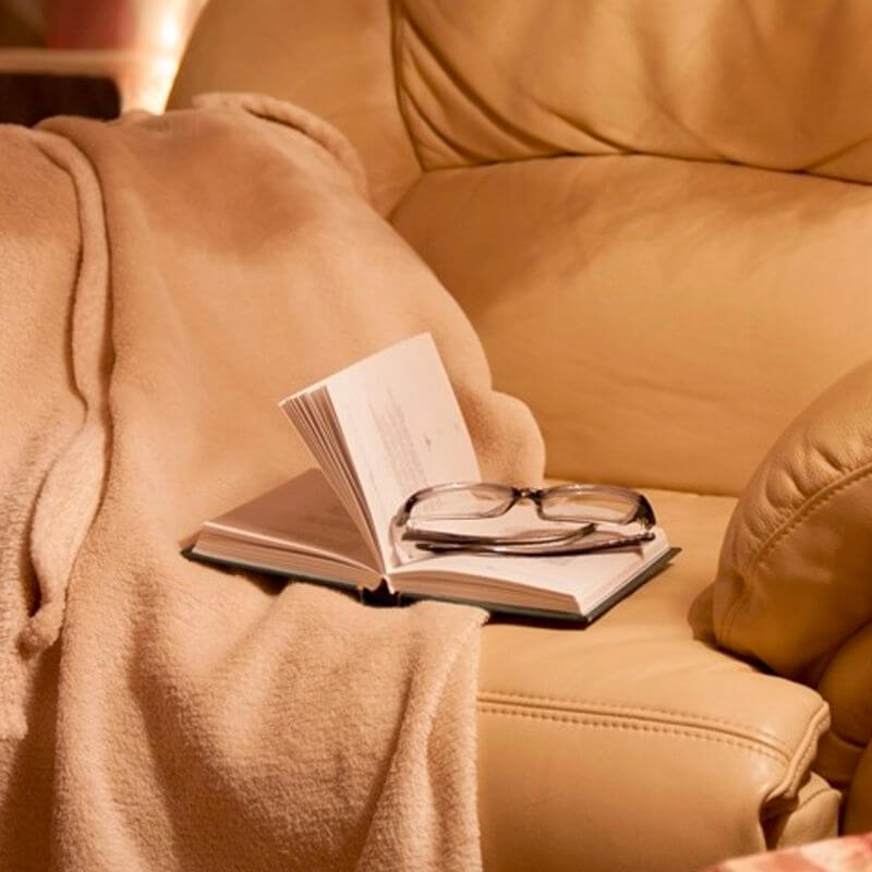 An empty and inviting armchair in neutral color with a book resting on it