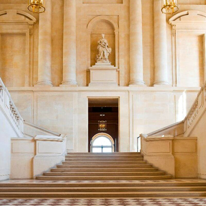 A palace with a central staircase leading to an opening in an impressive wall with pillars