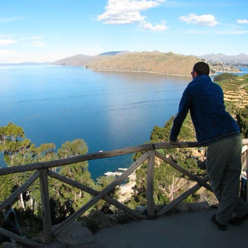 A man leans against a balcony railing, looking out at the view below