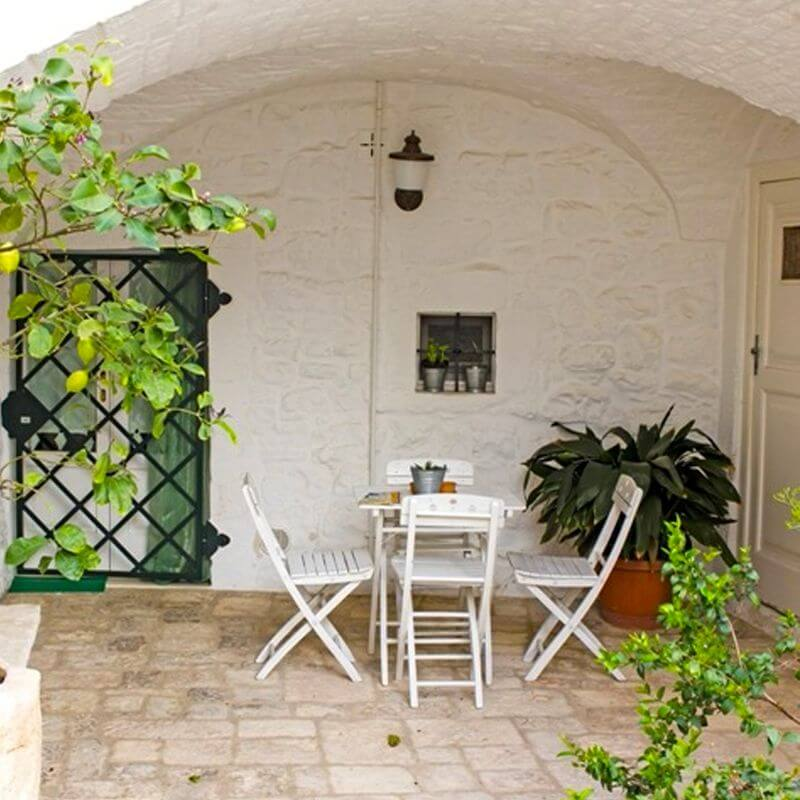 An outdoor seating area built in a stone niche with a arched ceiling