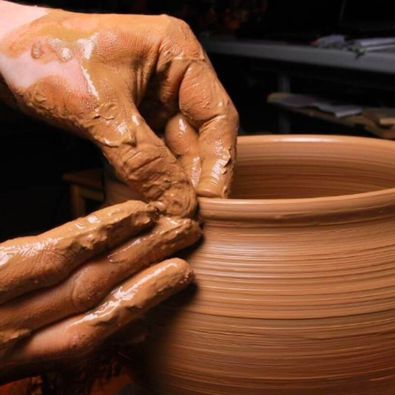 Closeup of hands working with clay and water to form a vase