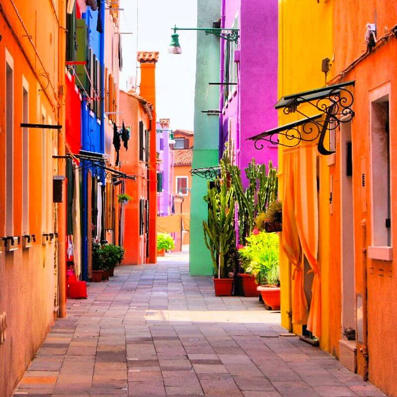 A colorful street walkway between tall street houses with bright colors