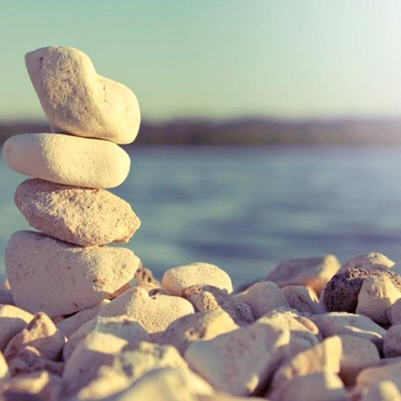 Three smooth stones stacked to form a small tower overlooking the sea