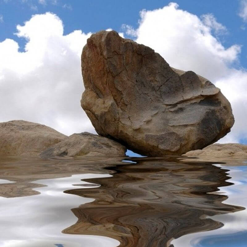 A large rock reflected in the clear sea water with soft white clouds behind it