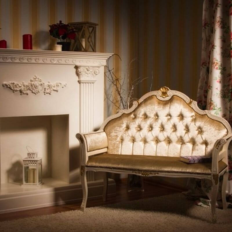 A fireplace decorated with cornice in a classical home with a Victorian sofa and a floral curtain behind it