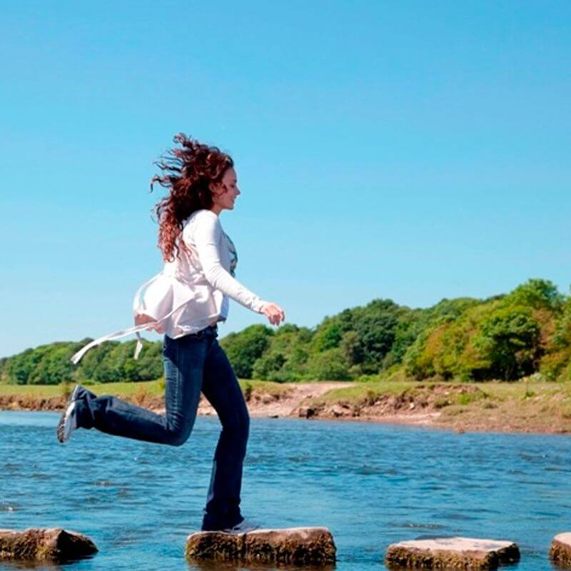 A girl jumps from rock to rock in the sea with a background of short green trees