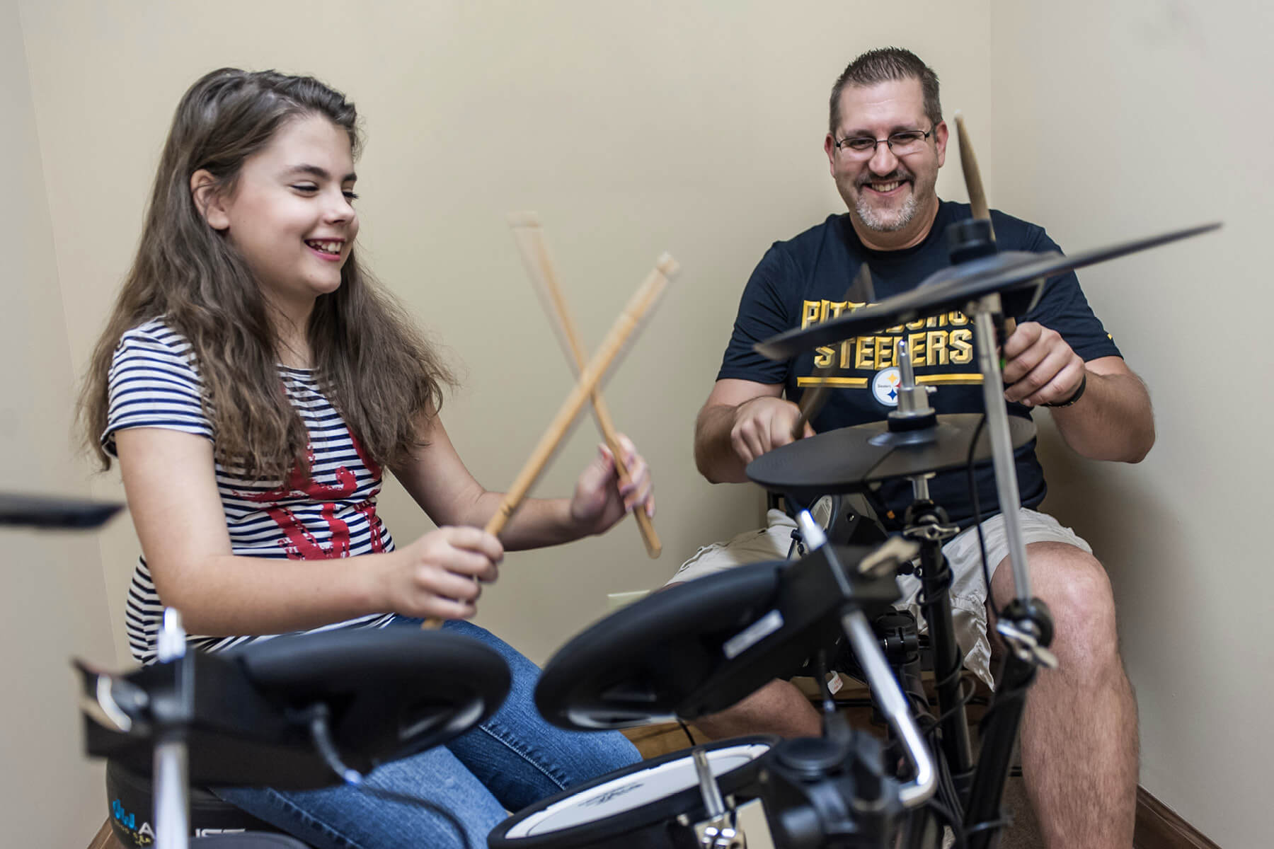 Student plays digital drum set with instructor.