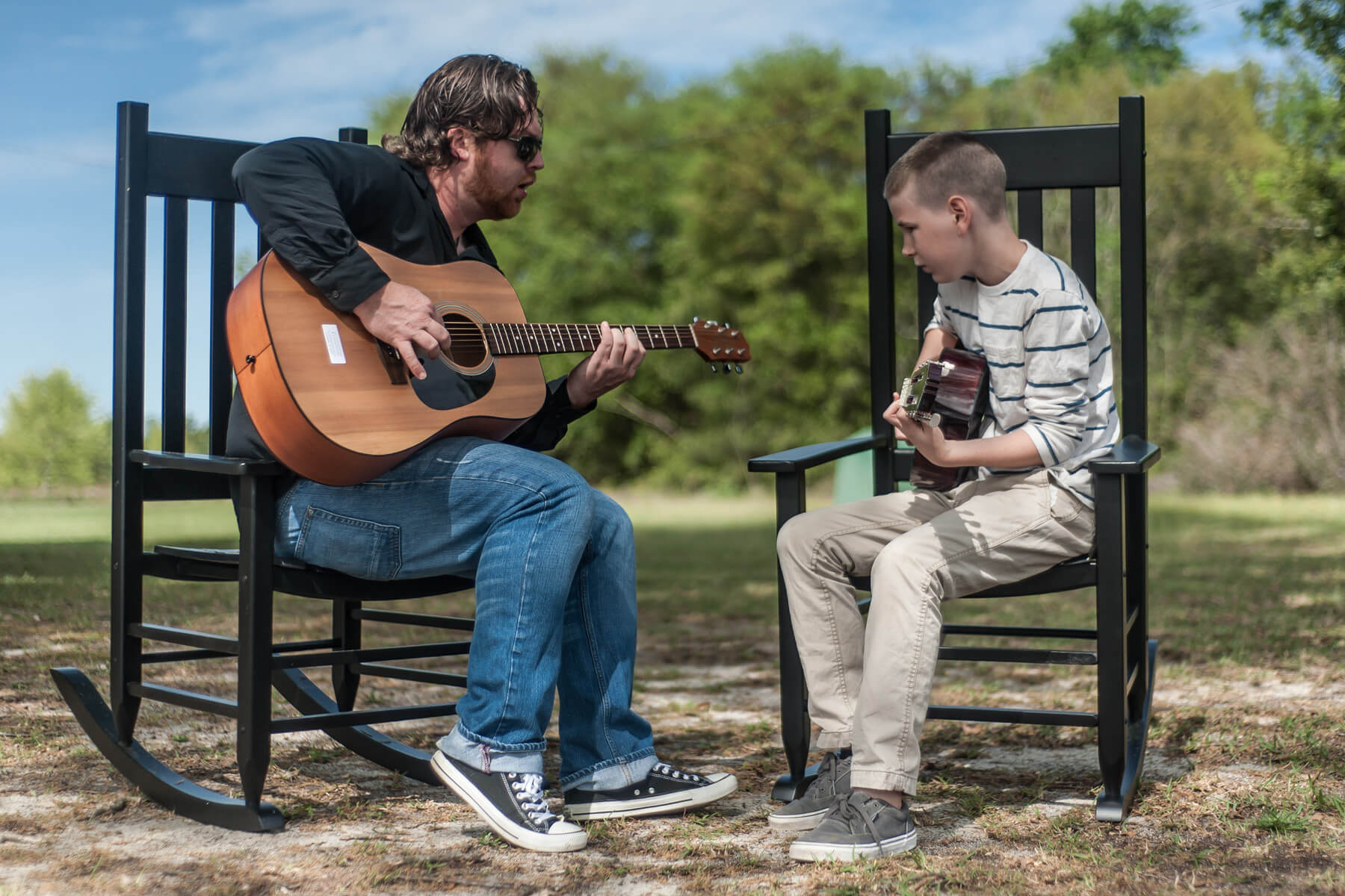 Student and instructor take guitar lesson outside