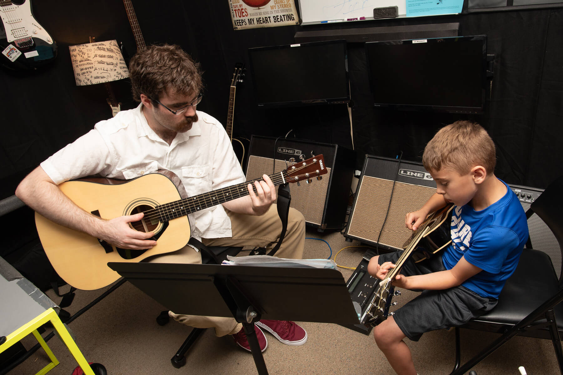 Instructor and student playing guitar