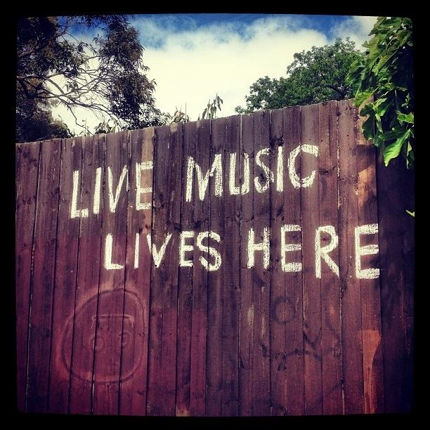 Image of a tall wooden fence with with the words Live Music Lives Here painted on it.t