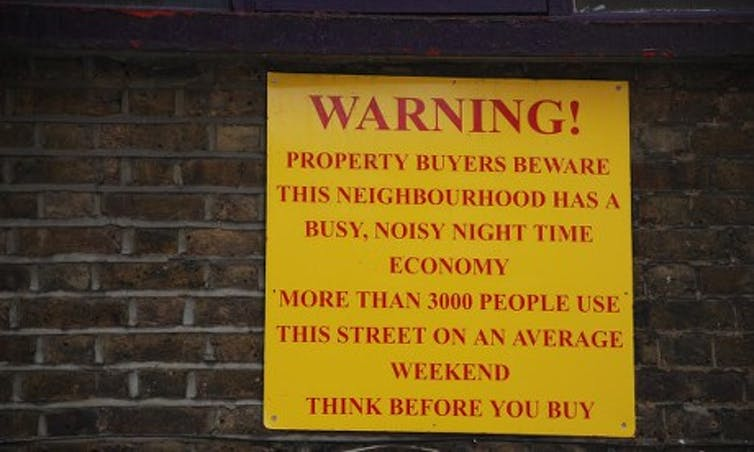 Image of a warning sign on a brickwall in Shoreditc, London. It reads Warning! Property buyers beware this neighbourhood has a busy, noisy night time economy. More than three thousand people use this street on an average weekend. Think before you buy.
