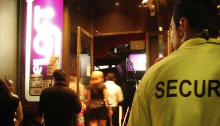 Image shows an individual security guard standing outside a venue with the word Security on the back of their shirt.