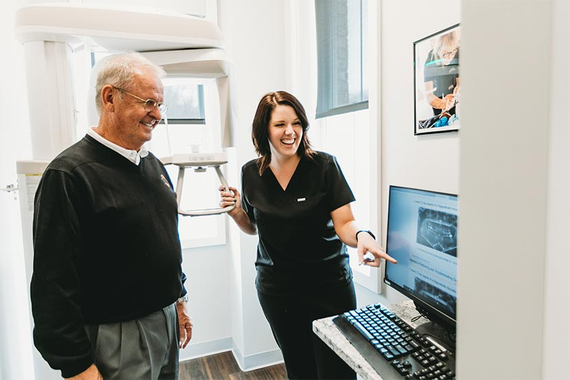Photo of a patient and a team member pointing to a computer screen
