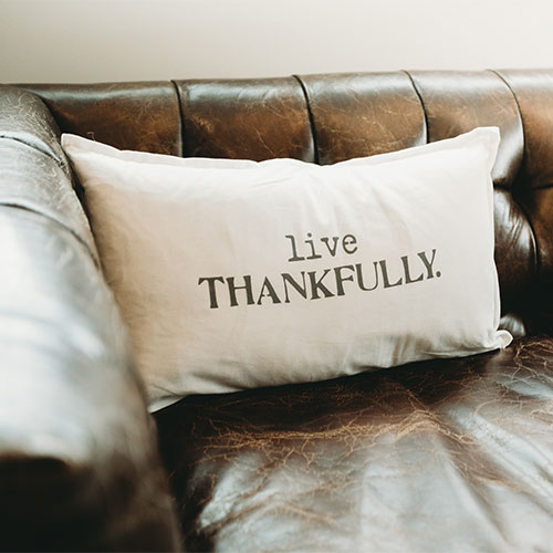 """Photo of a sofa and pillow that says, """"live thankfully."""""""