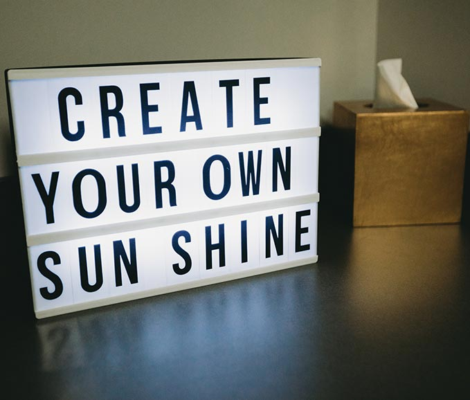 "Photo of a sign that says, ""Create your own sun shine"""