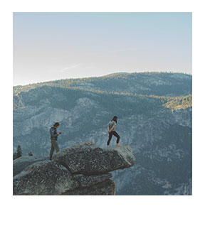 Hikers on the side of a cliff looking out