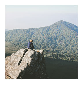Hiker on the side of a cliff looking out