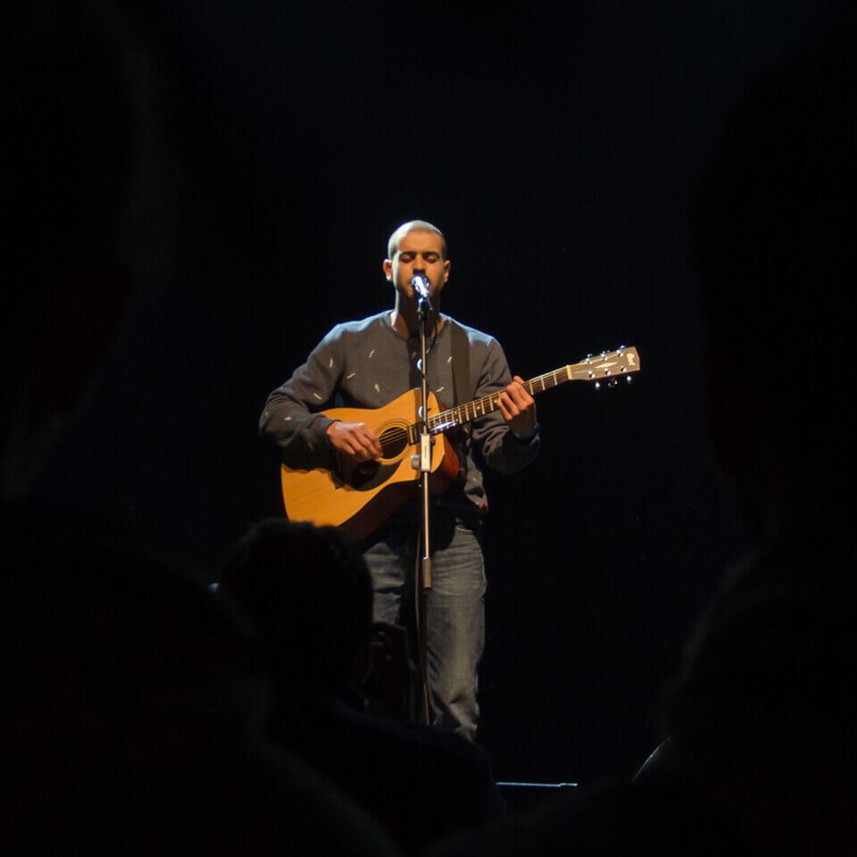 Denis Bustamante singing on stage