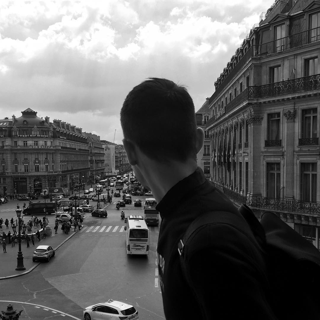 A black-and-white photo of Wilton Gorske looking over his right shoulder in Paris while wearing an Acne backpack and sweatshirt