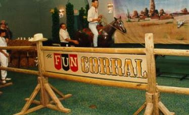 Participant mounts a life-size fiberglass horse and tries to rope the mechanical calf that shoots out from under the horse.
