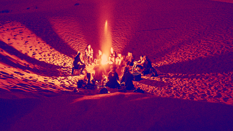 People gathered around campfire telling stories