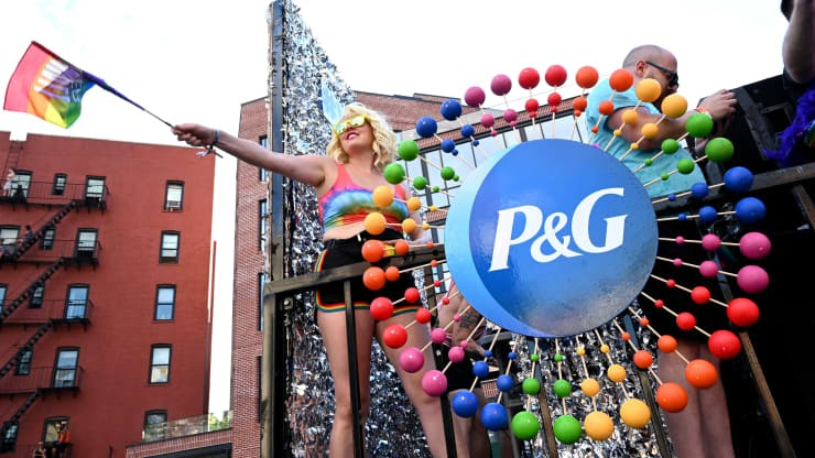People waving pride flags in front of Proctor and Gamble logo