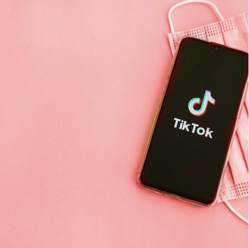 TikTok logo on pink background with medical mask