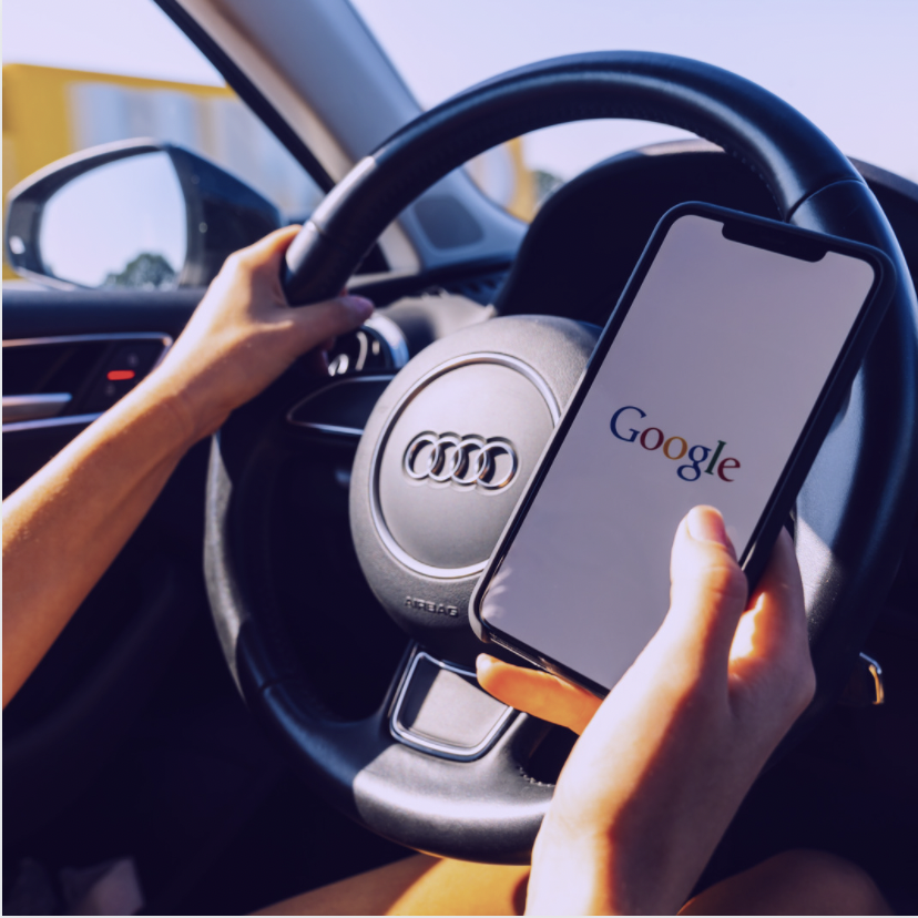 Person in car holding phone with Google chrome while driving Audi