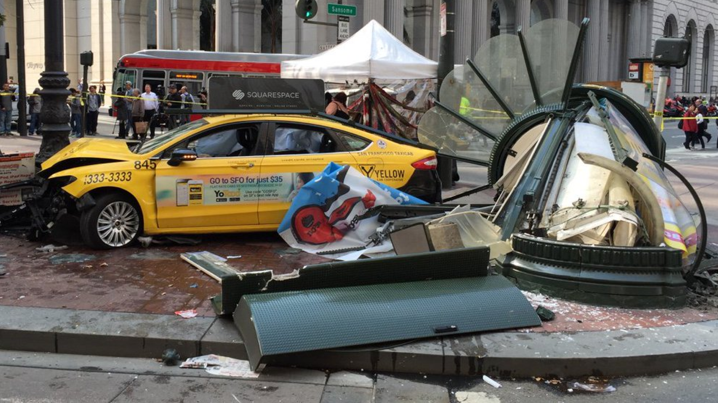 A taxi cab topped with a Squarespace advertisement crashes into a newspaper stand.
