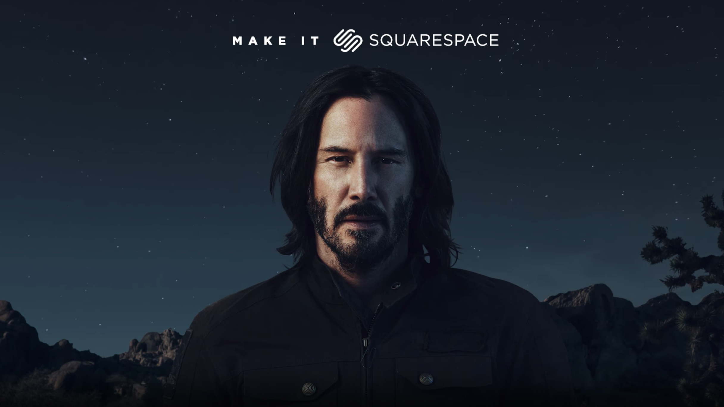 Keanu Reeves stands in front of a Joshua Tree at night during a Squarespace commercial.