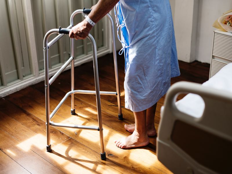 a knee replacement patient stands with the assistant of a walker beside their hospital bed