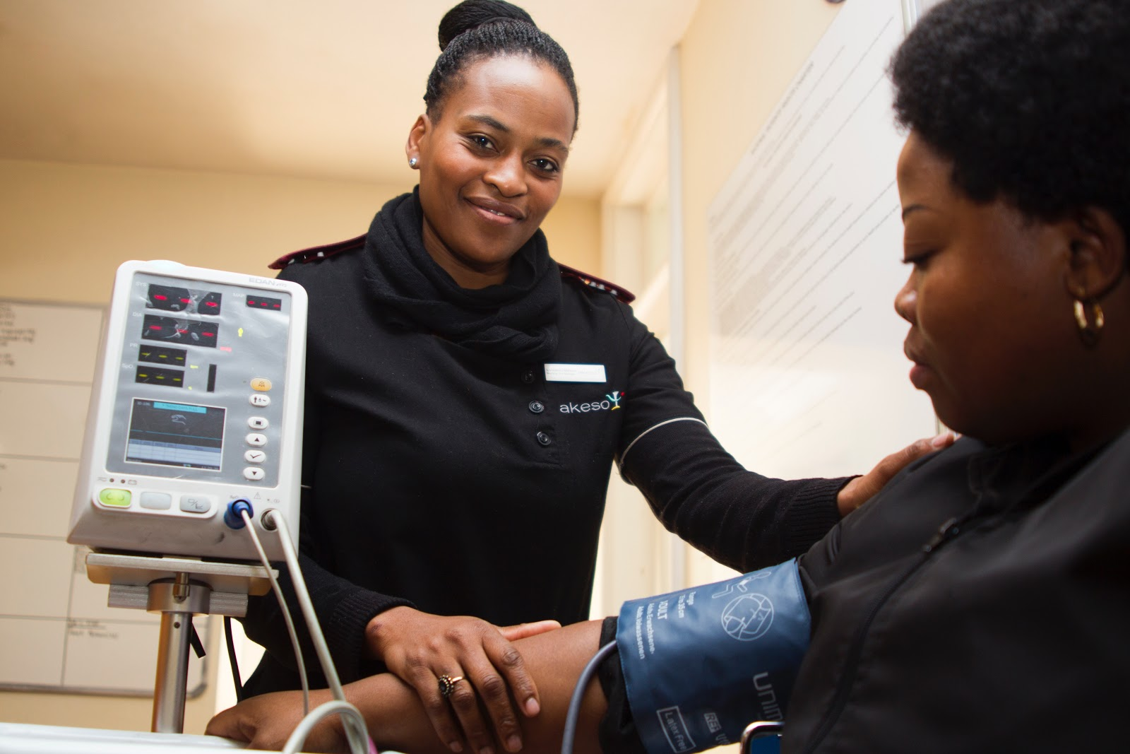 a technician smiles as she takes a patient's blood pressure