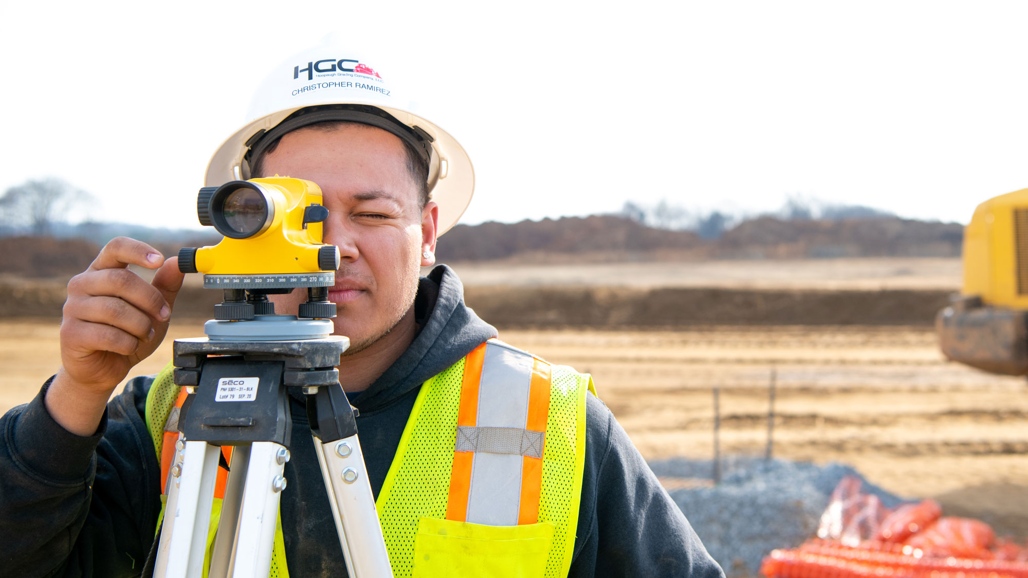Project team member using surveying equipment.