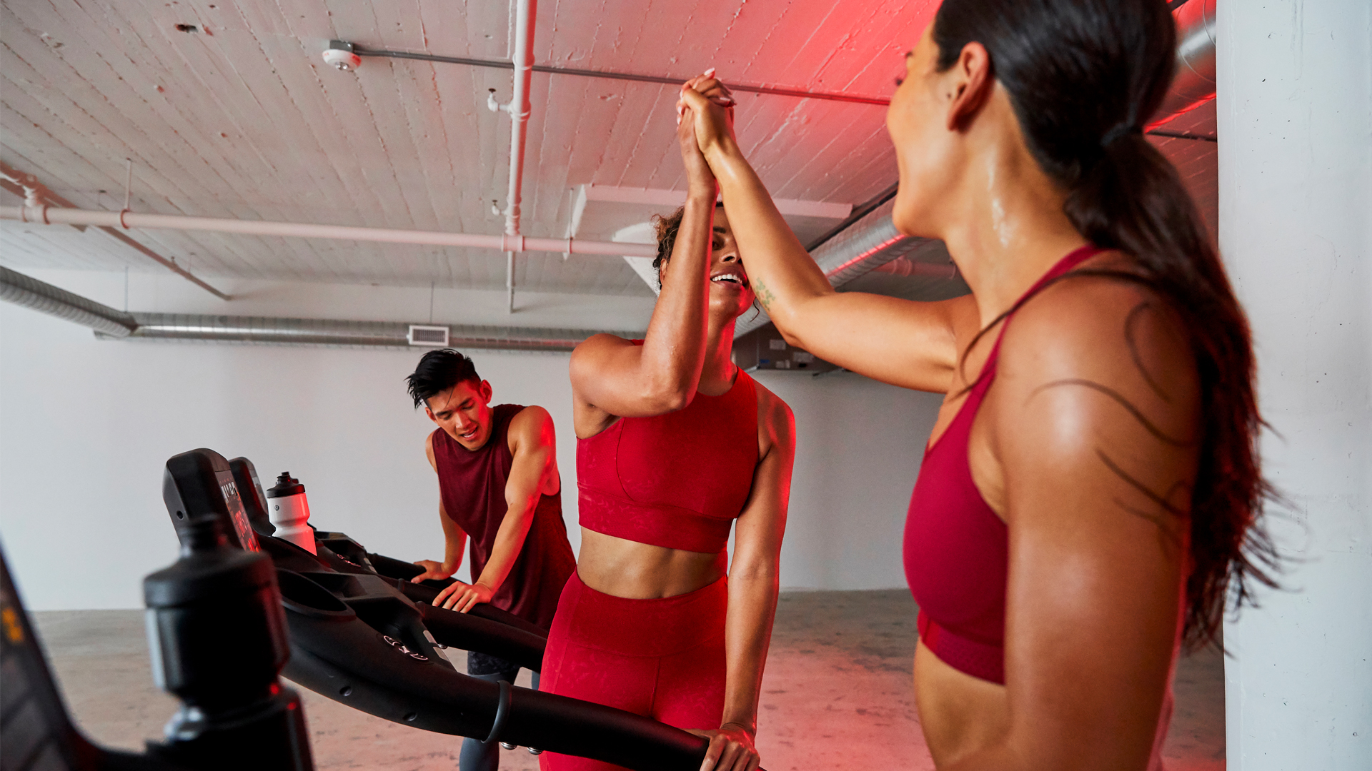 Studio photo of two woman wearing red workout clothes smiling and giving each other high fives on treadmills with tired man on treadmill behind them