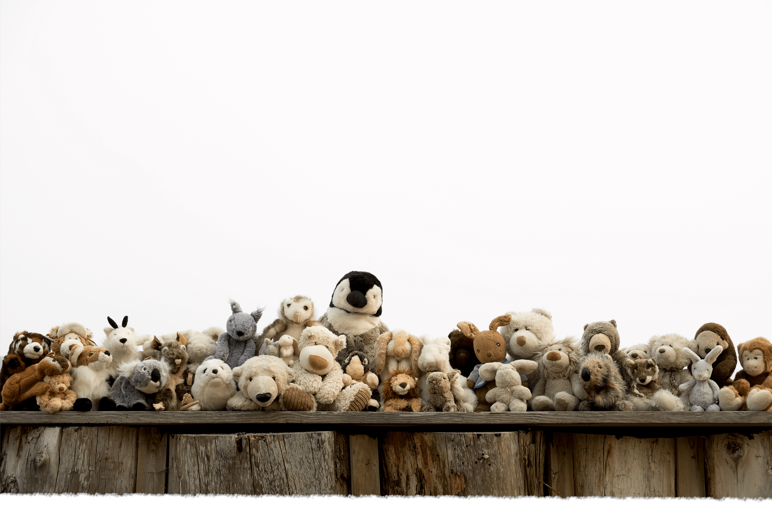 A large group of stuffed animals on top of a log wall