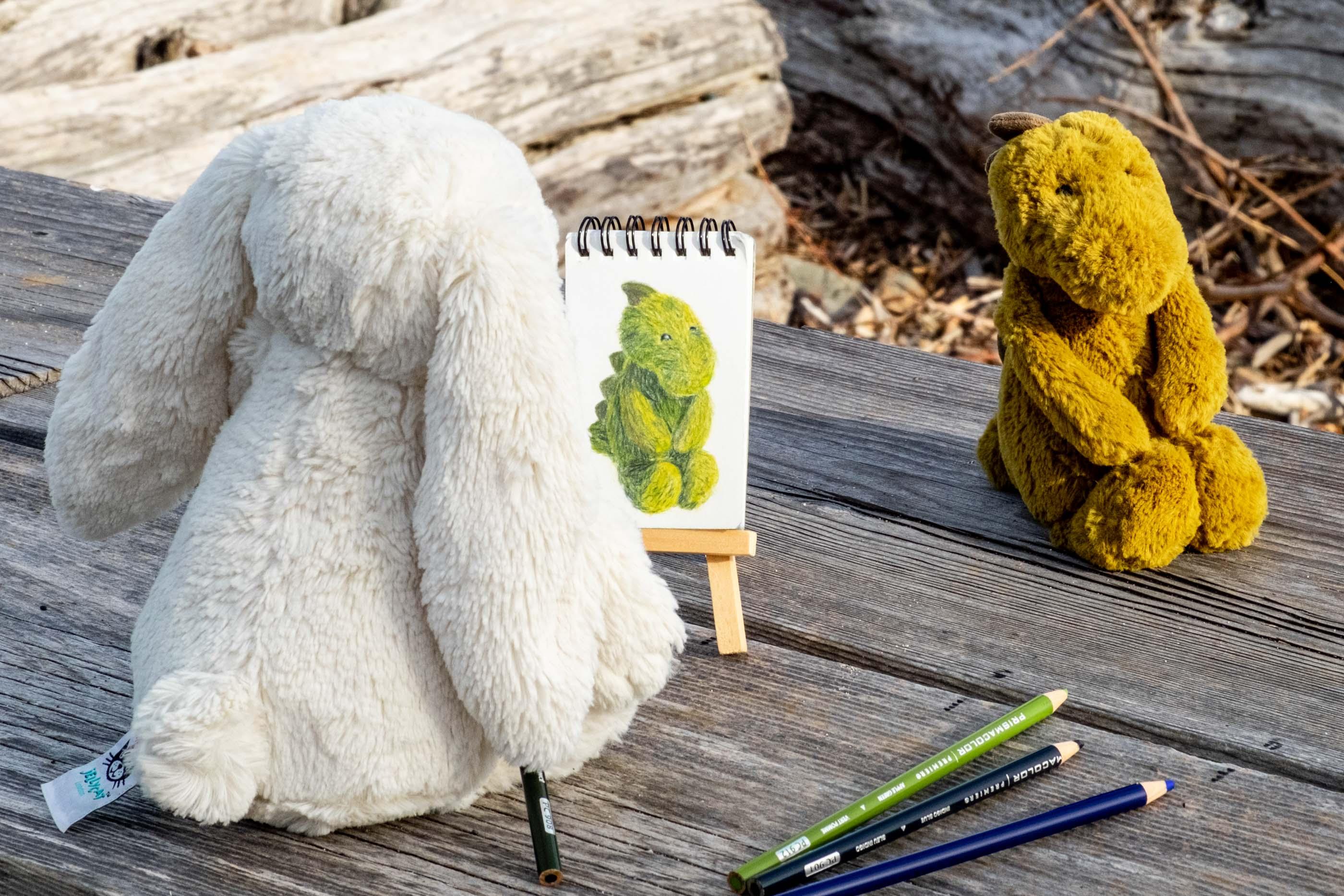 stuffed bunny drawing a portrait of a stuffed dinosaur