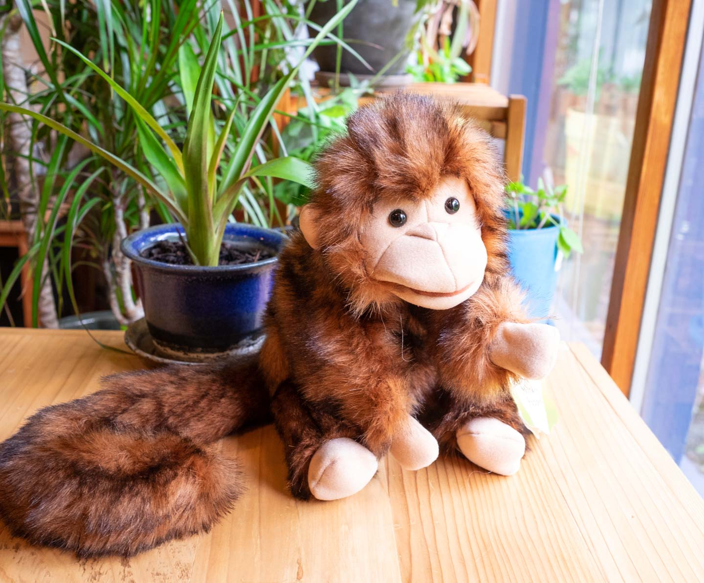 Brown monkey puppet with long tail