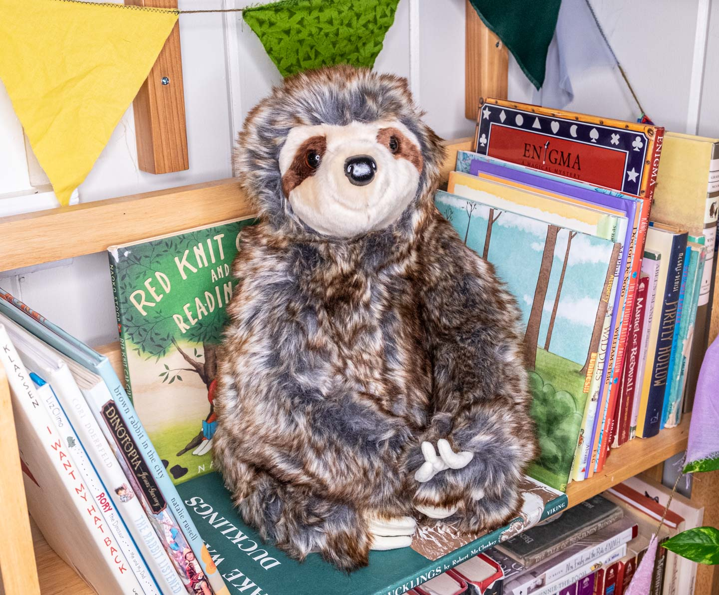 Smiling stuffed animal sloth in sitting position