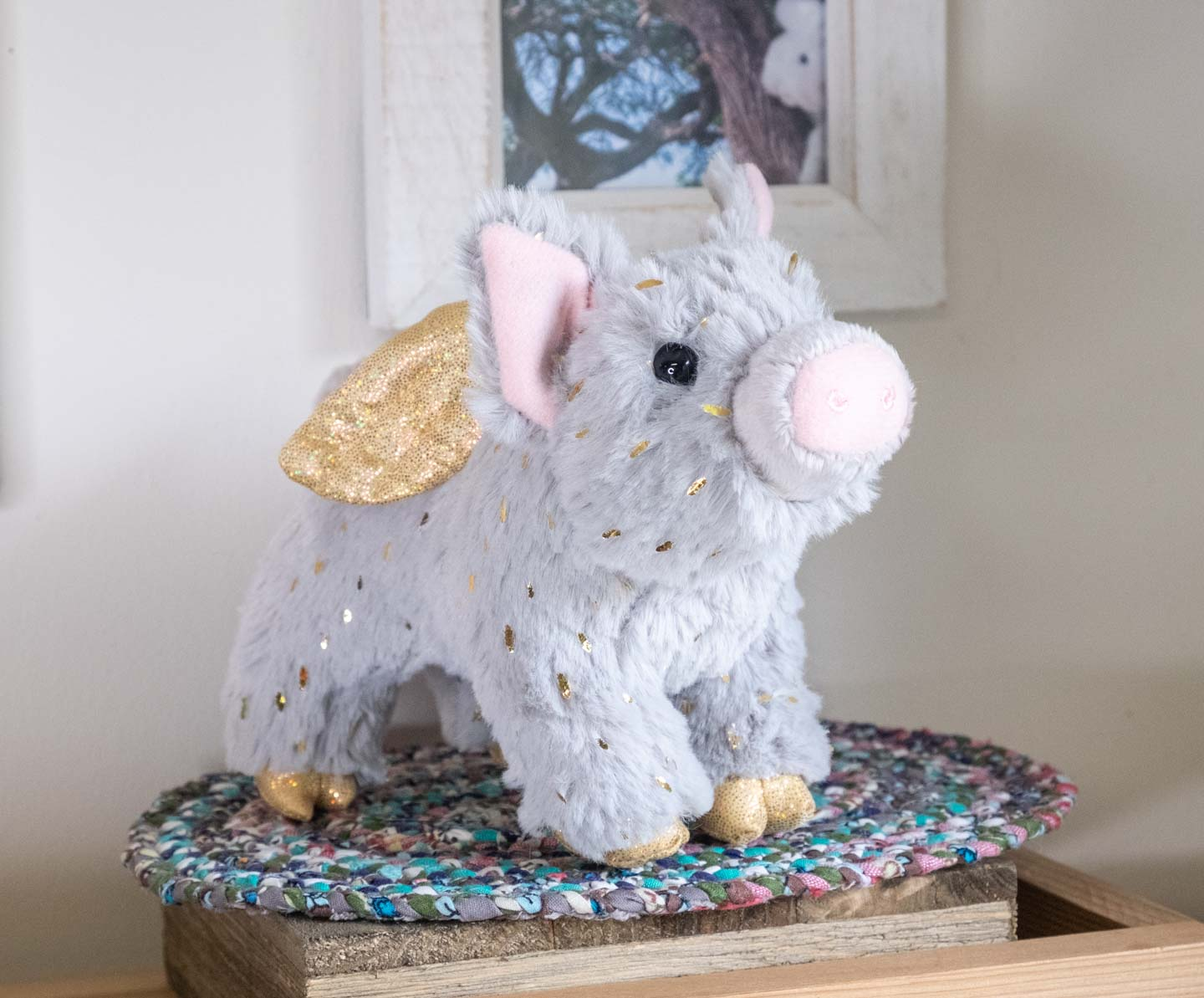 Gray stuffed pig with gold wings and gold hooves