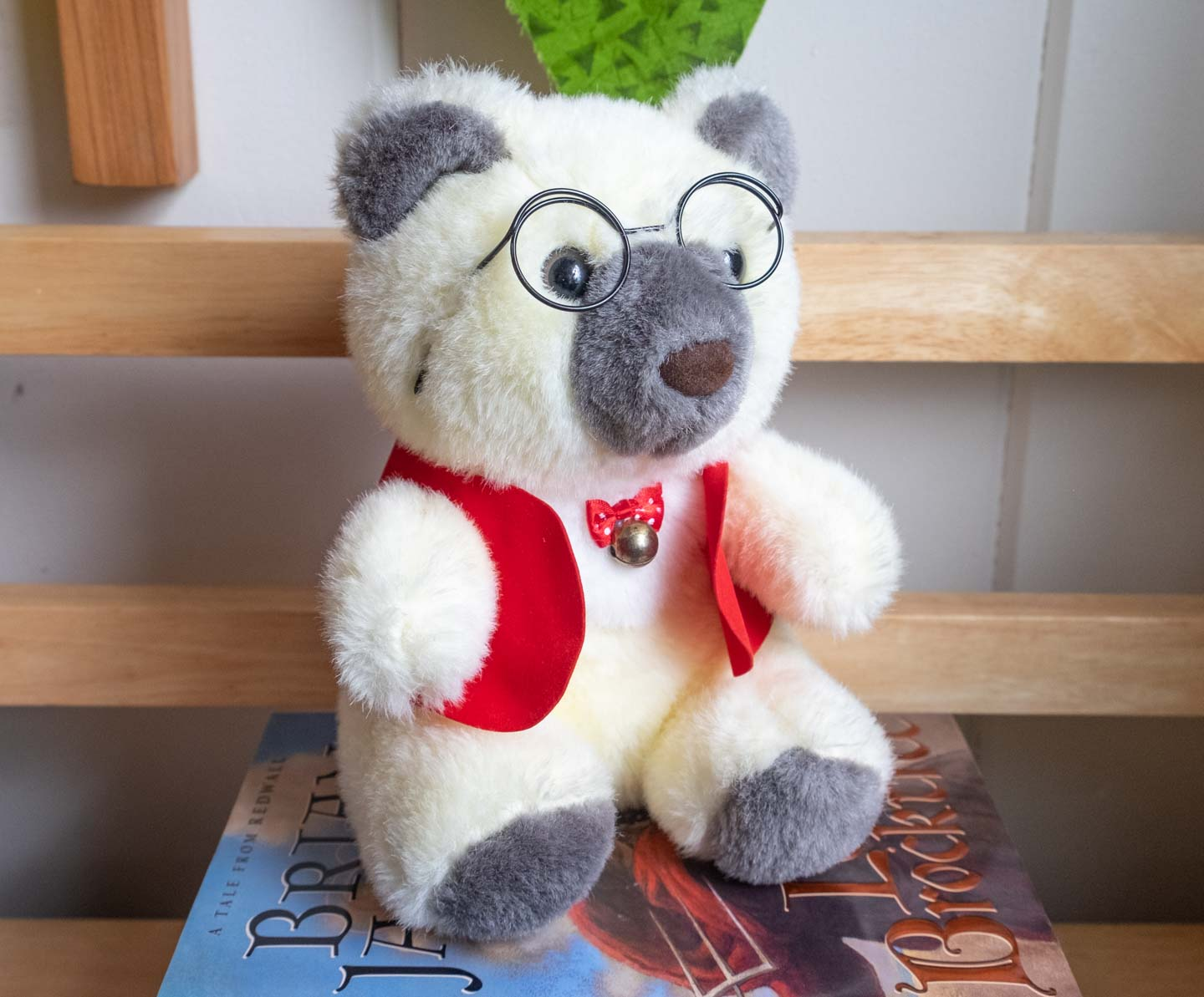 Cream and gray stuffed teddy bear wearing a red vest and wire glasses