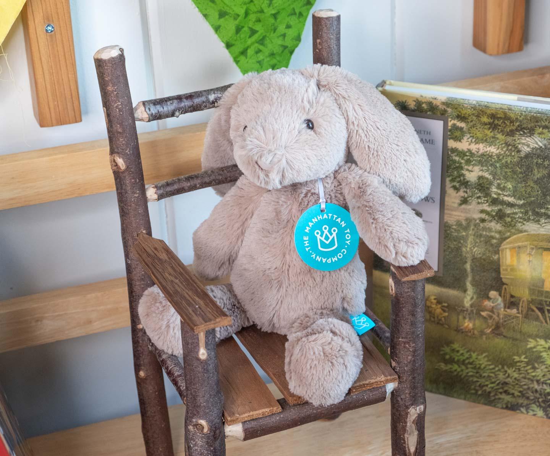 Floppy beige plush bunny sitting in a chair