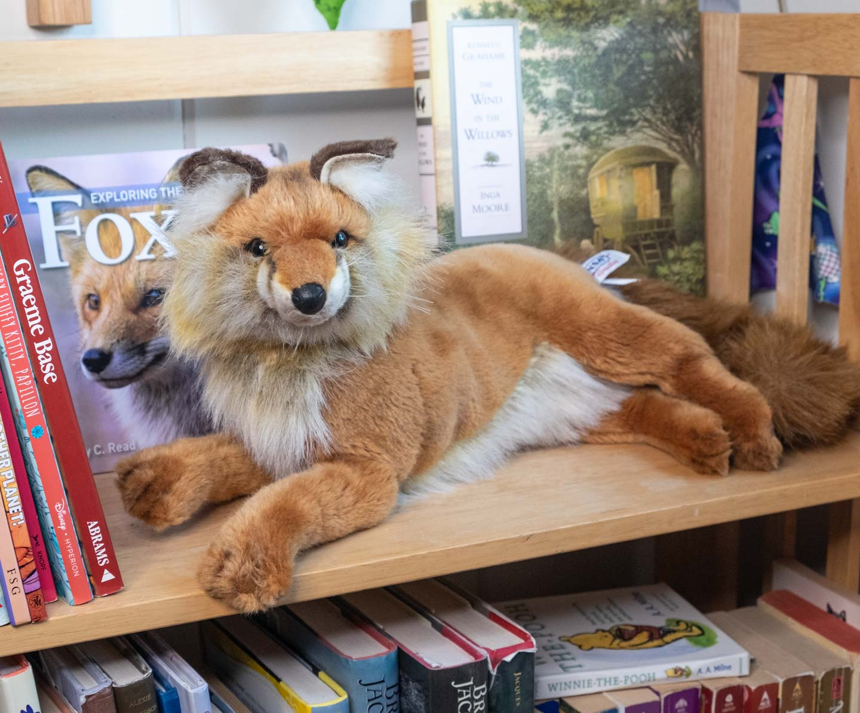 Hansa plush fox lying on a bookshelf