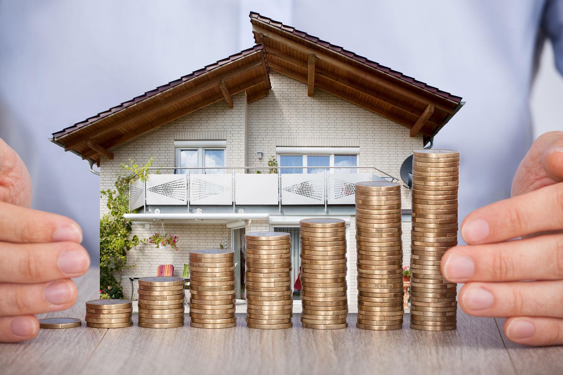 Modell von Haus mit Münzen