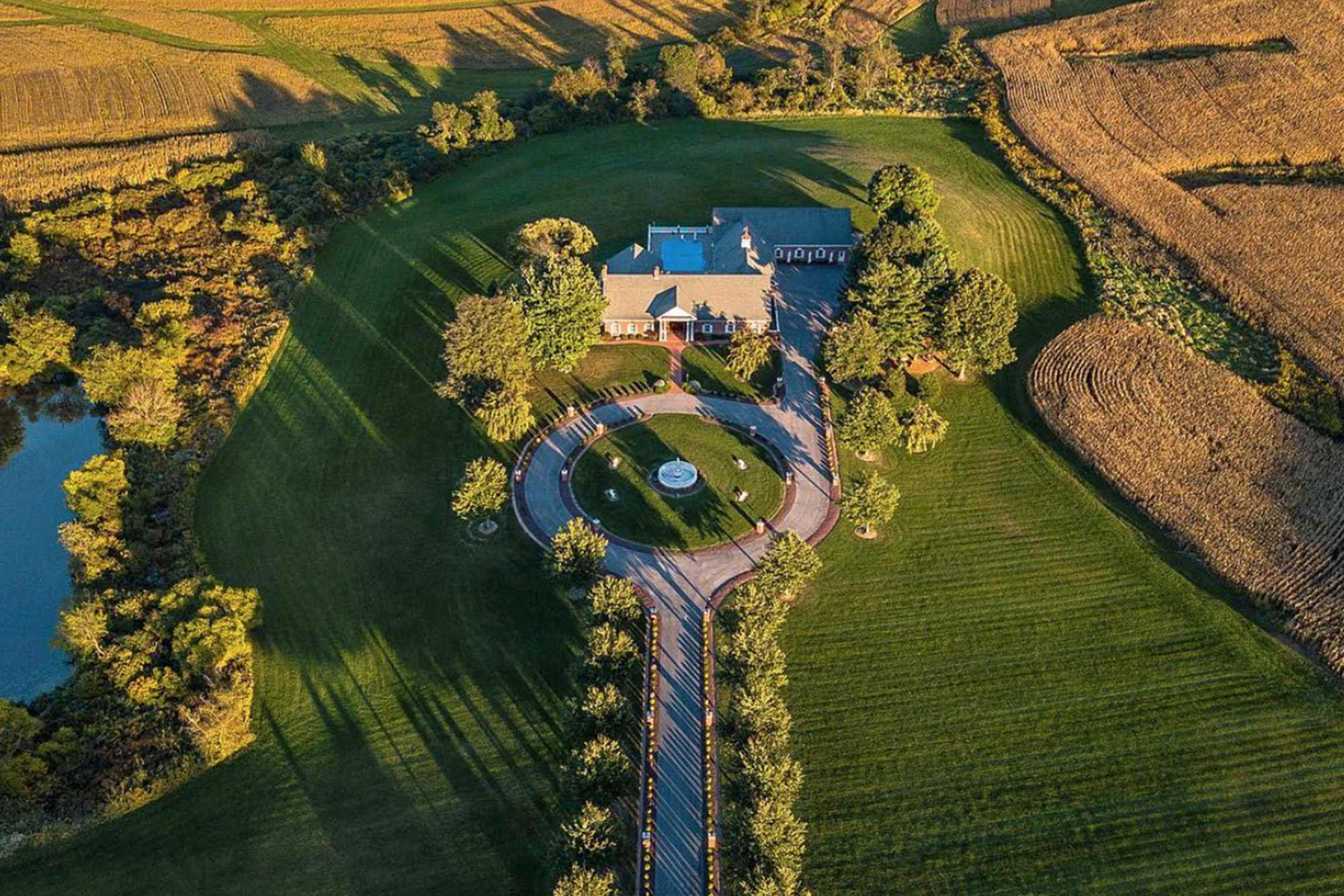 aerial view of mansion with circle driveway surrounded by corn fields and a large pond
