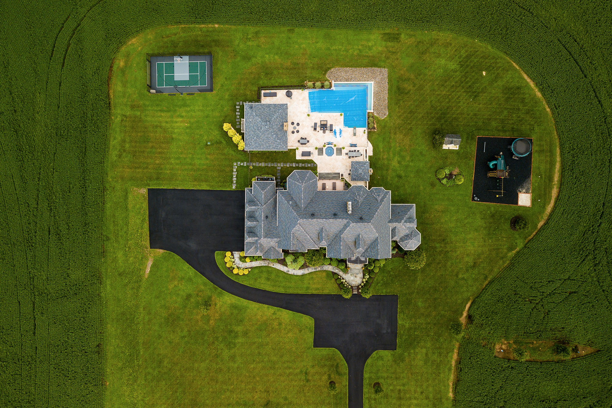 aerial view of large home with tennis court pool and playground