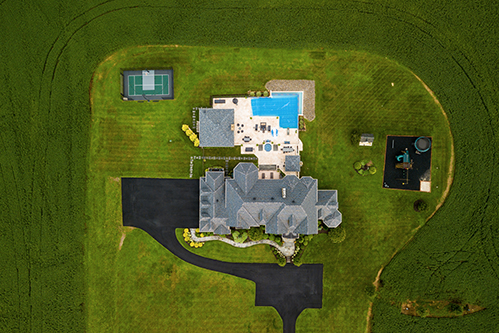 aerial view of mansion with pool tennis court and playground